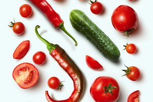 Red chili pepper, cucumber and tomato on white