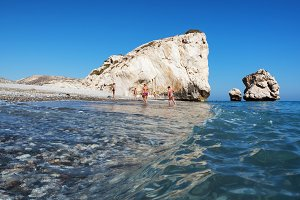 Paphos District, Cyprus - JULY 12, 2016: Vacationers near rocks Petra Tou Romiou (Aphrodite's Rock), low angle view