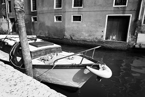 Old Boat Moored In A Narrow Canal Along Buildings, Venice, Italy