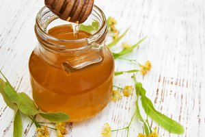 Jar with honey and linden flowers