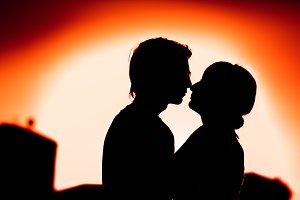 silhouettes of guy and the girl embracing on a background  the city
