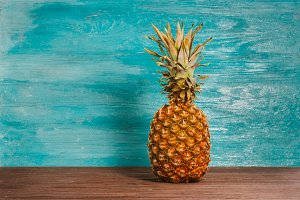 Pineapple is on the table a blue wooden background