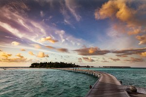 Wooden jetty towards a small island in Maldives at sunset