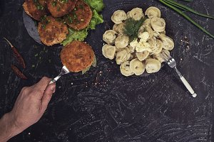 Fried cutlets and russian pelmeni on black background