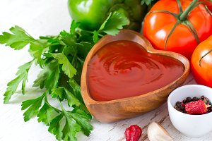 Tomato ketchup sauce in a wooden bowl and ingredients