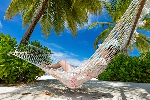 Woman lying on hammock between palms on a tropical beach. Maldives