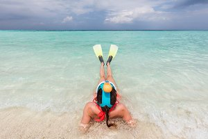 Woman wearing snorkeling mask and fins ready to snorkel in the ocean, Maldives.