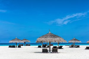 Sandy tropical beach with deckchairs and sunshades. Maldives