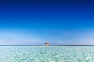 Tropical sandbank island with sunshade umbrella. Indian Ocean, Maldives.
