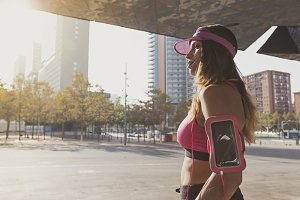 Woman listening to music on her smartphone sports armband in Barcelona