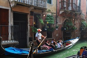 Venice, Italy - October 06, 2012: Tourists ride in a gondola in a side canal
