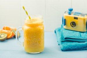 Beach gear, towel, orange smoothie and camera