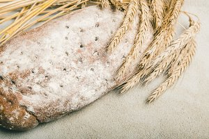 Ripe wheat with bread on grey rustic background