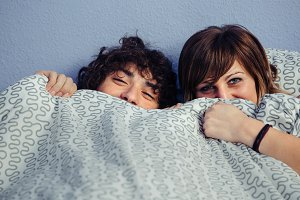 Happy couple laughing and covering mouths under duvet