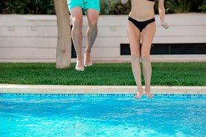 Close-up of girl and boy legs jumping into a swimming pool