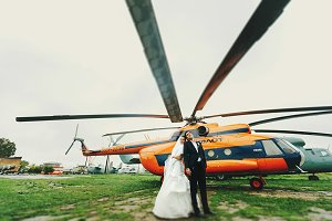 A wedding couple behind helicopters