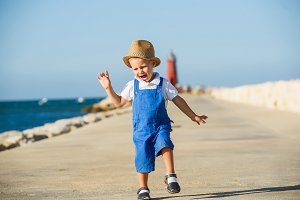 Cute blond boy in hat and blue overall