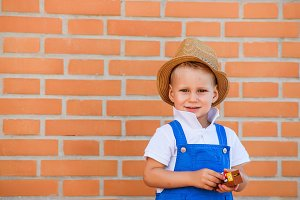 Small cute blond boy in overall and hat