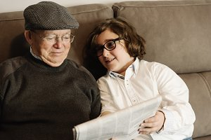 Grandpa and grandson reading news.