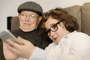Grandpa and grandson using mobile.
