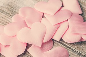 Pink hearts on textured wooden table. Toned square