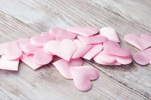 Pink hearts on textured wooden table