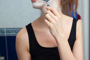 Funny girl shaving her face