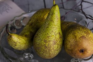 three fresh pears in glass vase on a dark background