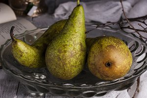 three fresh pears in glass vase on a dark background