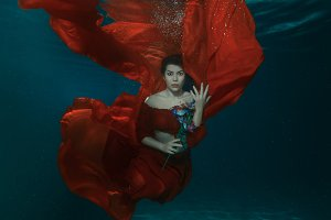 Woman in red dress underwater.