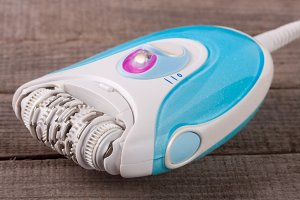 electric epilator hair on an old wooden background