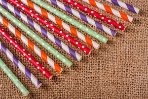 Colorful drinking striped straws on the background of burlap