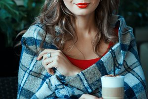 Beautiful girl sitting wrapped in a blanket, next to coffee.
