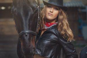 Girl cowboy standing near a horse.