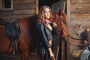 Girl in leather jacket with a horse.