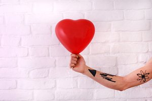 Tattooed hand with red heart balloon