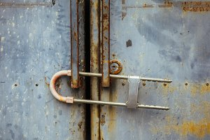 Close-up of rusty metal gate locked with security padlock