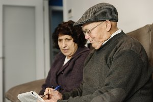 Elderly couple reading a newspaper.