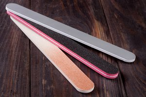 Three nail file with a different abrasive isolated on  dark wooden background