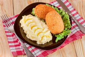 two fried breaded cutlet with mashed potatoes and lettuce on a black plate wooden background