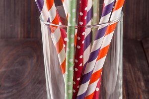 Colorful drinking striped straws in glass on a wooden table