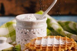 Waffles and sugar bowl with sugar powder