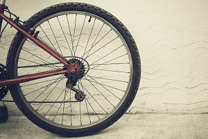 Red bicycle wheel beside wall