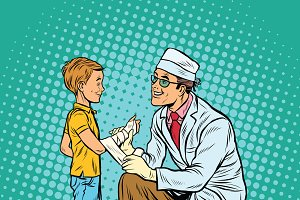 doctor bandaging boy injured arm