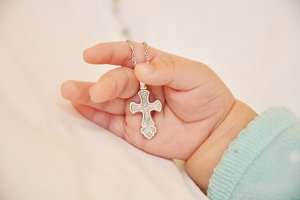 silver cross in baby hand
