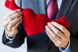 Businessman holding open armed heart with hands - warm welcome and invitation with heart concept