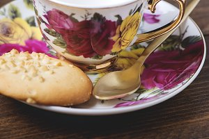 Porcelain cup with pretty ornaments next to some cookies on wooden table.