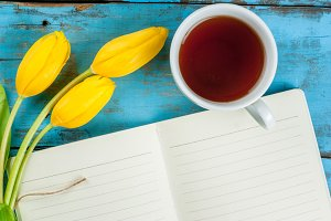 Tea with tulips and notebook