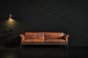 Brown leather couch in a dark room.