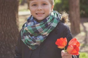 Boy holding bouquet of red tulips at spring time.